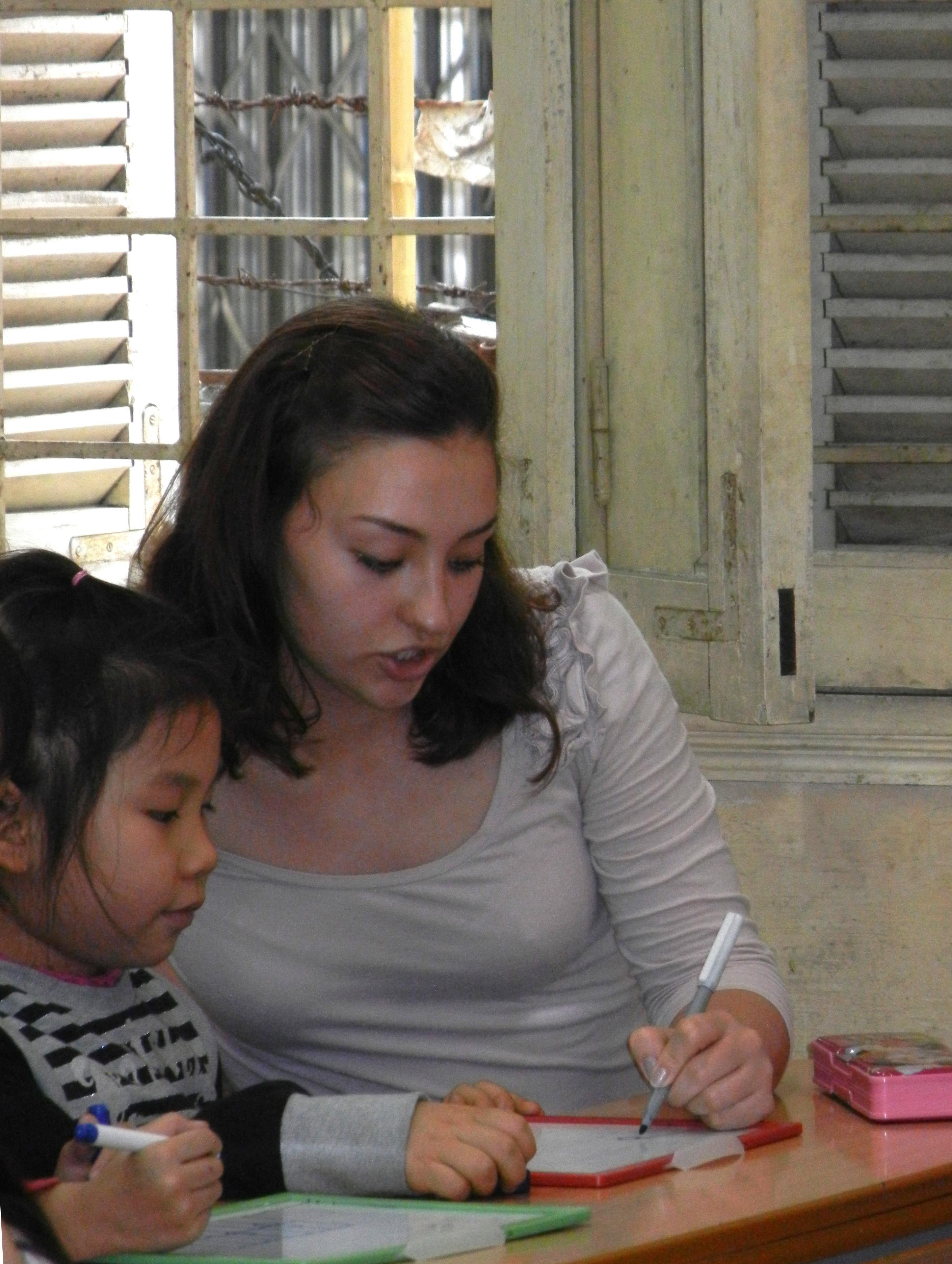 An intern from Projects Abroad can be seen teaching a child how to read and write whilst on her speech therapy internship in Vietnam.